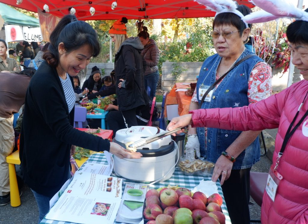 A woman serves an apple chip to a community member at Apple Festival